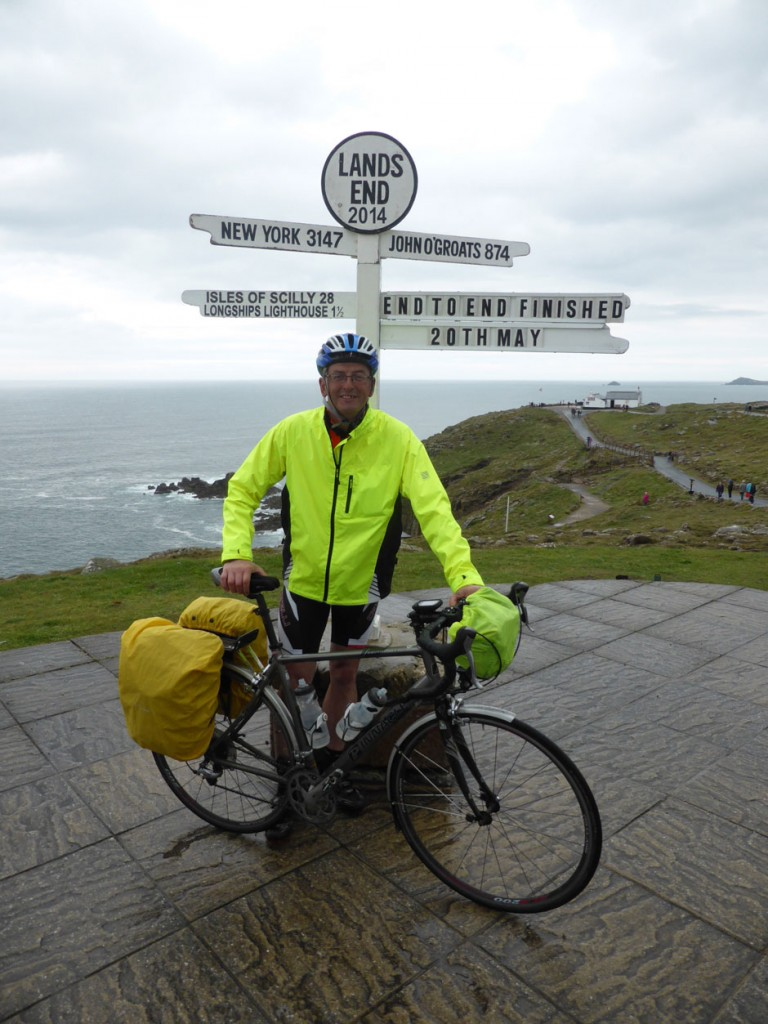 """Andrew Palmer standing with his bike underneath a sign  which reads """"Land's End 2014: End to end finished 20th May"""""""